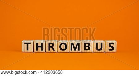Medical And And Thrombus Symbol. Wooden Cubes With The Word 'thrombus'. Beautiful Orange Background.