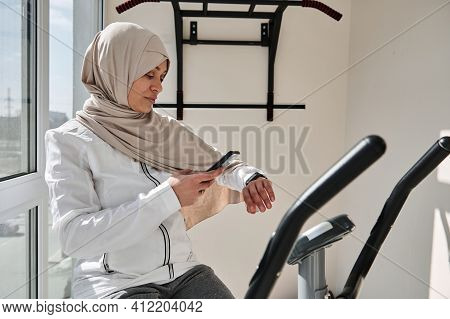 Muslim Fit Woman In Hijab Checking Her Fitness Track And Her Heart Rate After Cardio Workout On Stat