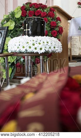 Black Urn On The Funeral Day In Church; Surrounded With Daisies And Roses