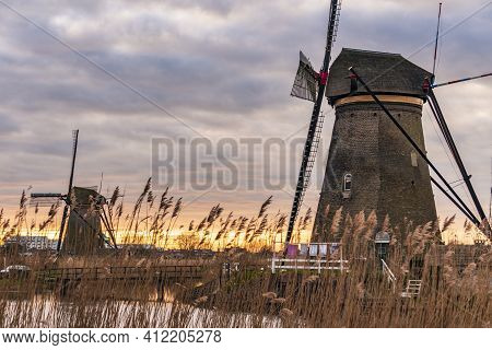 Dramatic Cloudy Sky Over The Famous Windmills In Kinderdijk Holland. Sunny Summer Evening At The Win