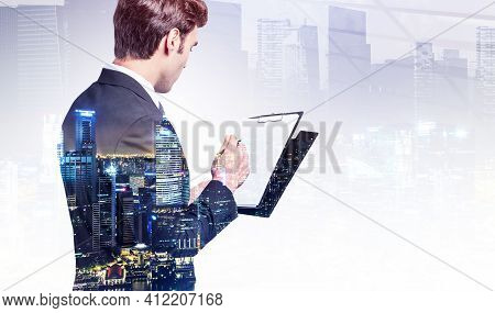 Office Man In Suit With Business Files, Double Exposure Of Business Buildings At Night. Concept Of B