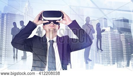 Young Handsome Businessman In Suit Holding Vr Glasses, Silhouettes Of Diverse Office People And Skys