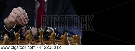 Strategy And Business Planning Concept. A Businessman At A Chessboard In Front Of Lined Up White And