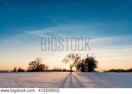 Dramatic Winter Sunset, Freezing Cold, Snow Covered. Clear Blue Sky At Winter Dusk. Fairy Winter Bac