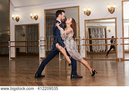Couple Practicing To Dance Tango In A Spacious Empty Hall, Reflected In The Mirror