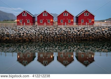 Classic Red Fishing Cottages In Perfect Symmetry Sitting Along A Stone Jetty With A Slightly Blurred