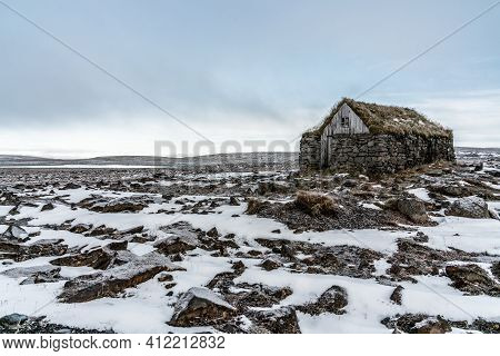 Remote Stone And Moss Roofed House In The Highlands Of Iceland. Snow And Rock Ground Surrounding Thi