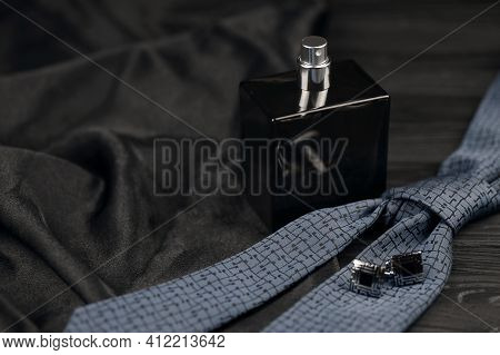 A Bottle Of Mens Cologne And Cufflinks With Blue Tie Lie On A Black Luxury Fabric Background On A Wo