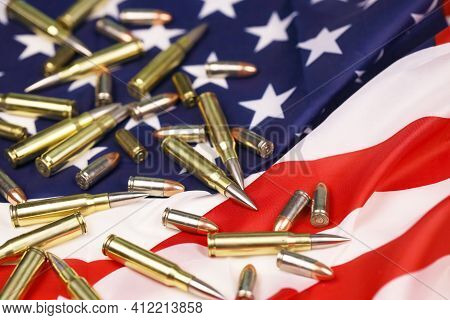 Many Yellow 9mm And 5.56mm Bullets And Cartridges On United States Flag. Concept Of Gun Trafficking