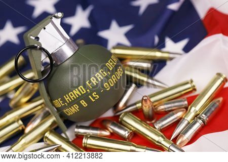 M67 Frag Grenade And Many Yellow Bullets And Cartridges On United States Flag. Concept Of Gun Traffi