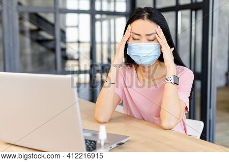Disappointed Female Worker Holding Her Head, Feeling Bad, In Medical Mask, Sitting In The Office At