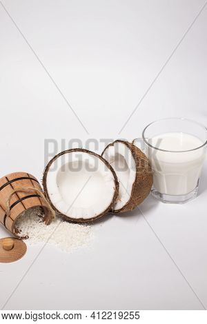 Opened Coconut Near Coconut Flakes In Wooden Bowl And Glass Of Coconut Milk Isolated On White Backgr
