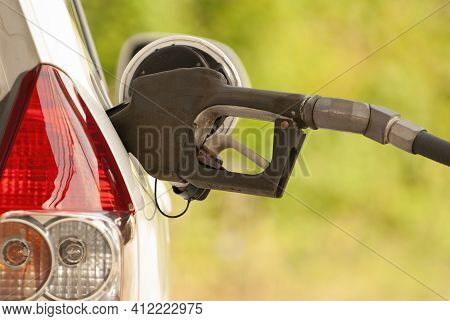 Horizontal Shot Of A Gasoline Nozzle In The Gas Tank Opening Of A Car.