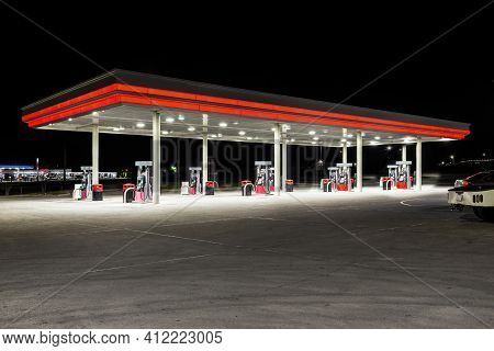Horizontal Shot Of A Generic Unbranded Gas Station At Night With Copy Space At The Top And Bottom.