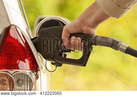 Horizontal Shot Of A Man's Hand Pumping Gas Into An Automobile.