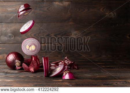 Flying Sliced ​​red Onion Rings, Whole Onion And Onion Peel On A Brown Wooden Background. Space For