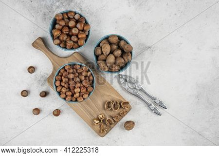 Bowls Of Walnuts, Hazelnuts And Kernels On Wooden Cutting Board