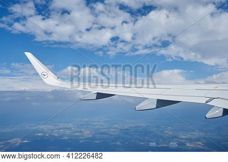 Munich, Germany - July 14, 2017: Left Wing Of The Aircraft Of Lufthansa In The Air With Clouds In Sk