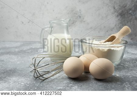 Flour, Eggs, Milk And Whisker On Marble Table