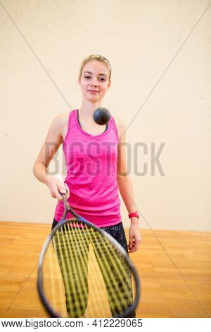 Cute young woman playing squash on a squash court, hitting the ball
