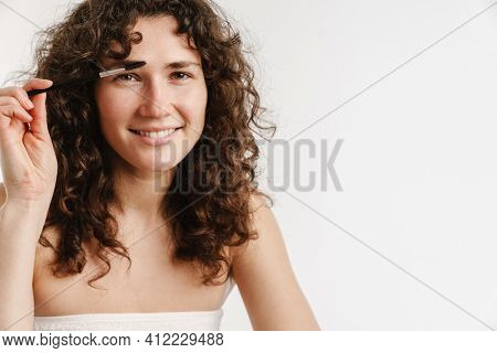 Half-naked curly woman smiling and using brow brush isolated over white background