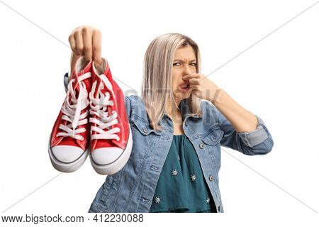 Young woman holding a pair of smelly sneakers isolated on white background