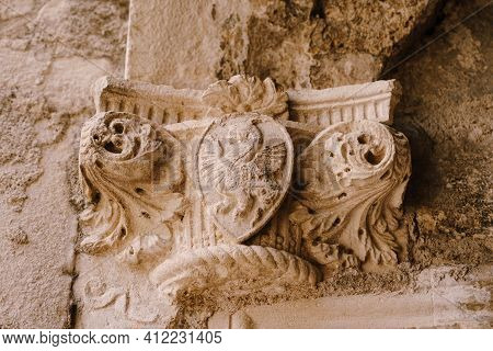 The Top Of A Bas-relief Column With A Shield Pattern Depicting A Dragon, In The Old Town Of Kotor, M