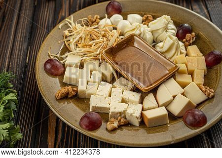 Cheese Assortment Plate On Dark Wooden Background, Free Space. Top View On Plate With Snack On For W
