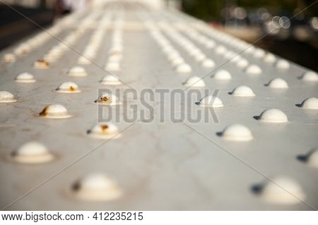 Selective Blur On White Metal Rivets On An Industrial Metallic Bridge, Some Old And Rusted. They Are