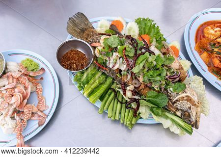 Fried Fish With Vegetable Top With Thai Seafood Salad Served With Chilli. Top View