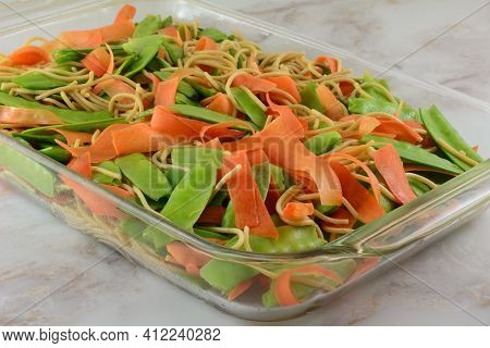 Raw Snow Peas And Carrot Peels And Cooked Pasta Casserole Layers For Cooking In Glass Baking Pan