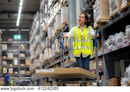 Warehouse Workers Check Stock Details In Storage Area Putting Them On Shelves. Work In Distribution
