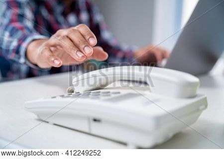 Close Up Hand Of Businessman Is Picking Up The Phone Receiver In Office.