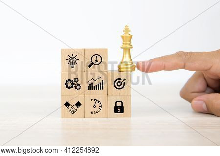 Hand Choose King Chess On Wooden Toy Blocks Stacked With Graph And Business Planning Icon. Concepts