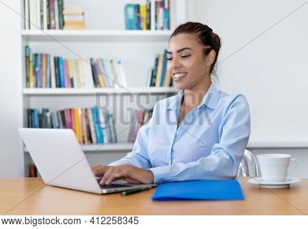 Beautiful Latin American Business Trainee Working At Computer At Desk At Office
