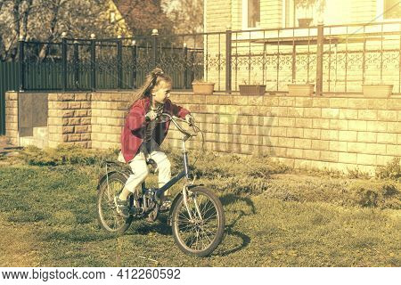Girl Riding A Bike Near The House. Girl On Bicycle Smiling While Ride. Little Girl Enjoying Bike Rid