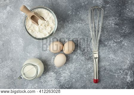 Bowl Of Flour, Eggs And Whisker On Marble Surface