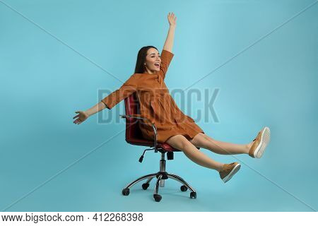 Young Woman Riding Office Chair On Turquoise Background