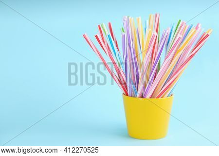 Colorful Plastic Drinking Straws In Holder On Light Blue Background, Space For Text