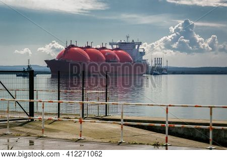 Lng Tanker - Ship And Tugs Are Maneuvering At The Gas Terminal