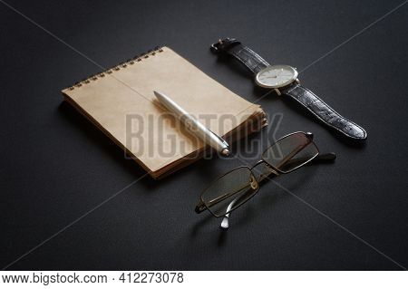 Notebook Made Of Eco-friendly Paper, Diary, Glasses, Ballpoint Pen And Wrist Watch Lie On A Black Ta