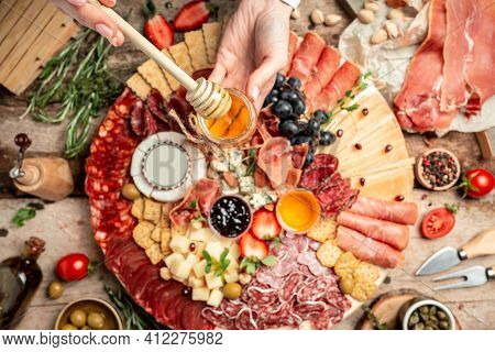 Antipasto With Traditional Spanish Meat Snacks On Wooden Board. Women's Hands Holding Honey, Antipas