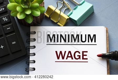 Minimum Wage - Word Is Written In A Notebook With A Marker, Calculator, Clamps And Cactus. Business