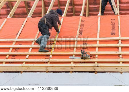 Irpin - Ukraine, March - 13, 2021: Roofing Contractor Takes Measurements Before Installing Roof Boar