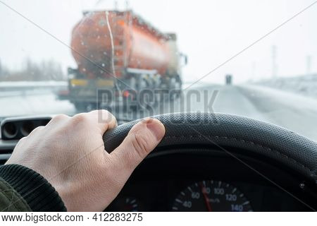The Driver Hand On The Steering Wheel Of The Car, Which Is Overtaken On The Secondary Line By A Tank