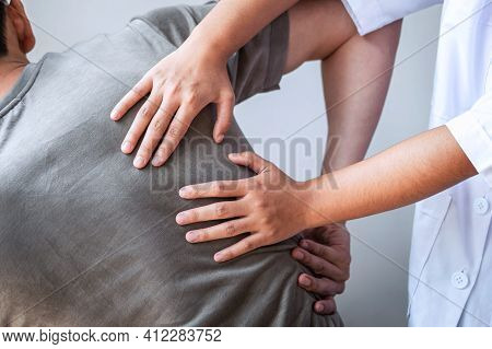 Doctor Or Physiotherapist Working Examining Treating Injured Back Of Athlete Male Patient, Doing The