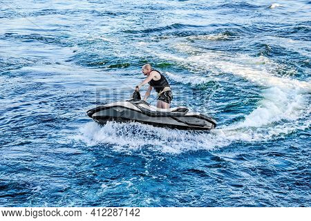 Kherson, Ukraine - July 22, 2020: A Young Man Cuts The Waves On A Jet Ski In The Dnieper River In Kh