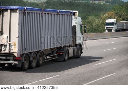 two trucks drive towards each other on the road, cargo transportation, shipping concept