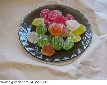 A Bunch Of Multicolored Marmalade Sprinkled With Sugar On A Black Plate