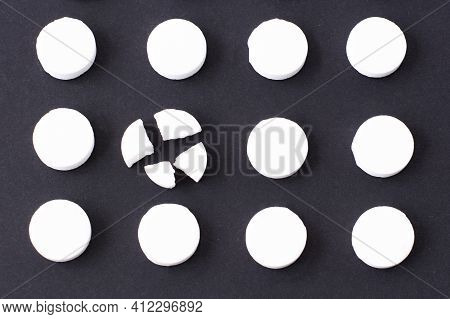 Round White Medical Pills Arranged In Square Order And One Of Them Is Crushed Into Four Parts